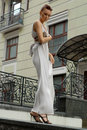 Brunette in long dress near a hotel Royalty Free Stock Photo
