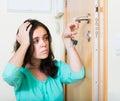 Brunette looking at broken lock of door Royalty Free Stock Photo