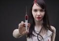 Brunette nurse with syringe and red liquid Royalty Free Stock Photo