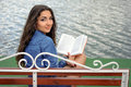 Brunette reading a book on a bench girl in denim shirt with near the pond Stock Images