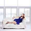 Brunette relaxing on sofa full length portrait of beautiful young woman in blue dress and jewellery with large windows Royalty Free Stock Photography