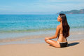 Brunette sitting on the beach in a lotus position travel Royalty Free Stock Photo
