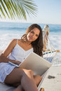 Brunette sitting on hammock with laptop smiling at camera the beach Royalty Free Stock Photography