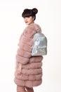 Brunette smiling teen girl in pink fur coat advertise backpack, Royalty Free Stock Photo