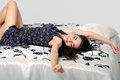 Brunette stretches after sleep beautiful girl lying on the bed Stock Images