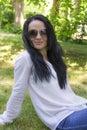 Brunette in sunglass sitting on green grass european woman Royalty Free Stock Photo