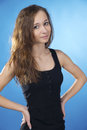 Brunette teen with arms akimbo on blue woman Royalty Free Stock Images