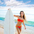 Brunette teenager surfer bikini girl with surfboard on beach shore Stock Photography