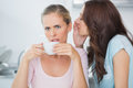 Brunette telling secret to her friend while drinking coffee in the kitchen Royalty Free Stock Photography