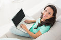 Brunette using her laptop on sofa Royalty Free Stock Photo