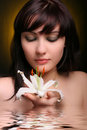 Brunette with white lily flowers in water Stock Photo