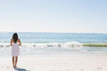 Brunette in white sun dress standing by the water on beach Royalty Free Stock Photography