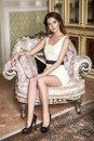 Brunette woman in beige dress in classic luxury rich interior at