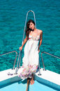 Brunette woman in dress standing on bow of yacht and looking at camera Royalty Free Stock Images