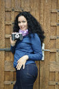 Brunette woman with film photo camera collection taking pictures girl her in front of an wooden vintage door Stock Photography