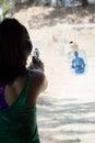 Brunette woman firing pistol at firing range