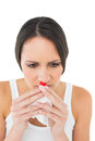 Brunette woman having a nose bleed on white background Stock Photography