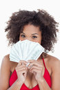Brunette woman hiding her face behind a fan of notes Stock Photos
