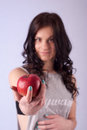 Brunette woman holding a red apple outstretched hand Royalty Free Stock Photo