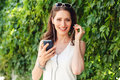 Brunette woman inserts earpiece into her ear and holding phone Royalty Free Stock Photo