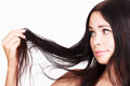Brunette woman is not happy with her fragile hair white background copyspace Royalty Free Stock Photos