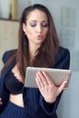 Brunette woman online flirt on tablet in office Stock Image