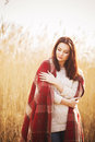 Brunette woman outdoors in check pattern plaid smiling Royalty Free Stock Photo