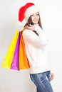 Brunette woman in santa hat holding shopping bags Stock Images