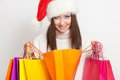 Brunette woman in santa hat holding shopping bags Royalty Free Stock Photo