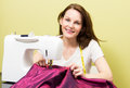 Brunette woman sewing european diy at home in front of yellow background Royalty Free Stock Photos