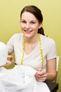 Brunette woman sewing european diy at home in front of yoellow background Stock Photo