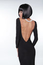 Brunette woman with sexy back in black dress posing at studio vogue style fashion haircut Stock Images