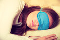 Brunette woman sleeping in blue eye sleep mask Royalty Free Stock Photo