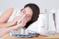 Brunette woman sneezing in a tissue in the living room and pills on bedside table Royalty Free Stock Photo