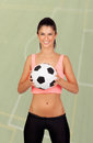 Brunette woman with a soccer ball on field of background Royalty Free Stock Photography