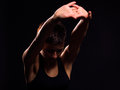 Brunette woman stretching and exercising against a backlit black background Royalty Free Stock Photos