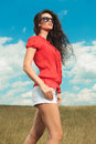 Brunette woman walking in the fields with hands in pockets Royalty Free Stock Photo