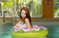 Brunette woman in a water floating tube Royalty Free Stock Photography