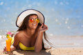 Brunette woman white hat drink cocktail beautiful fun and joy smiling in yellow bikini and orange in tropical blue sea water has Stock Photos