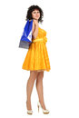 Brunette in a yellow dress with shopping bags beautiful young over white Stock Photos