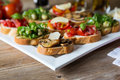 Bruschetta with beans and arugula mushrooms goat cheese on a wooden board Stock Photos