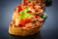 Bruschetta with cheese and tomatoes on a black background Stock Images