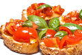 Bruschette italian appetizer fresh homemade crispy called bruschetta topped with tomato garlic and basil on white background Royalty Free Stock Photos