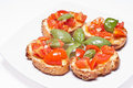 Bruschette italian appetizer fresh homemade crispy called bruschetta topped with tomato garlic and basil on white background Stock Image