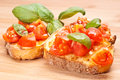Bruschette italian appetizer fresh homemade crispy called bruschetta topped with tomato garlic and basil on wooden board Royalty Free Stock Photo