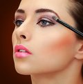 Brush applying eye shadows on beauty woman face closeup portrait brown background Royalty Free Stock Photography