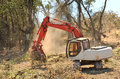Brush hoe track excavator clearing trees and from a hillside in preperation for a new commerical construction development Royalty Free Stock Photos