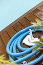 Brush and leaf skimmer beside swimming pool wall maintenance tools on deck Stock Photography