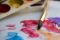 Brush on the paper with drawing next to artistic paint closeup. Royalty Free Stock Photo