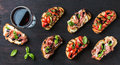 Brushetta snacks for wine. Variety of small sandwiches on dark rustic wooden backdrop